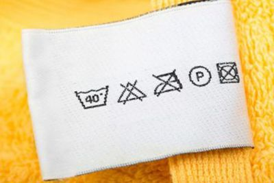 Ετικέτα με οδηγίες φροντίδας σε κίτρινη πετσέτα.