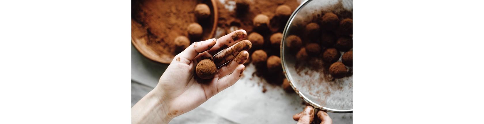 Eine mit Kakao beschmutzte Hand hält eine frischzubereitete Schokopraline, im Hintergrund verschwommen Pralinen in Schüsseln und teilweise auf dem Tisch verteilt.