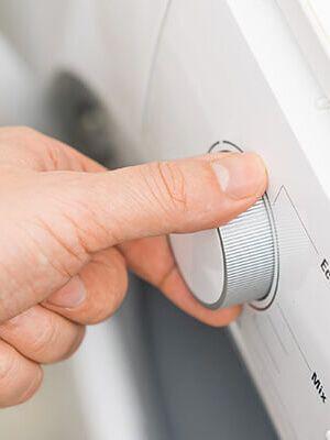 Un main qui choisit le programme de la machine à lavée
