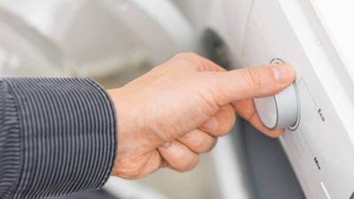 Ansicht einer  Hand, die ein Waschprogramm auswählt.