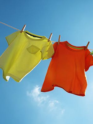 Tricou galben si rosu prins pe sârma de rufe, cerul albastru in fundal.