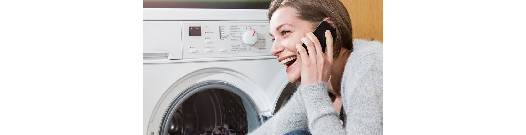 Eine lachende Frau sitzt vor einer Waschmaschine und telefoniert.