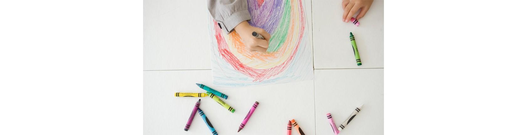 Eine Kinderhand malt mit bunten Wachsmalstiften.