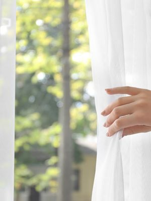 hand hält weiße gardine vor  einem fenster mit blick auf grüne  laubbäume zur seite