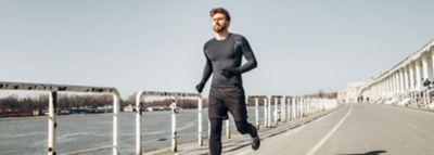 Moški teče v črnih športnih oblačilih.