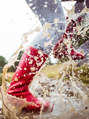 Füße in pinkfarbenen Gummistiefeln treten kräftig in eine mit Schlamm gefüllte Wasserpfütze.