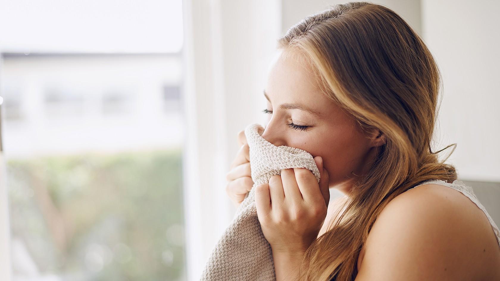 Eine Frau genießt mit geschlossenen Augen den Duft frischgewaschener Wäsche.
