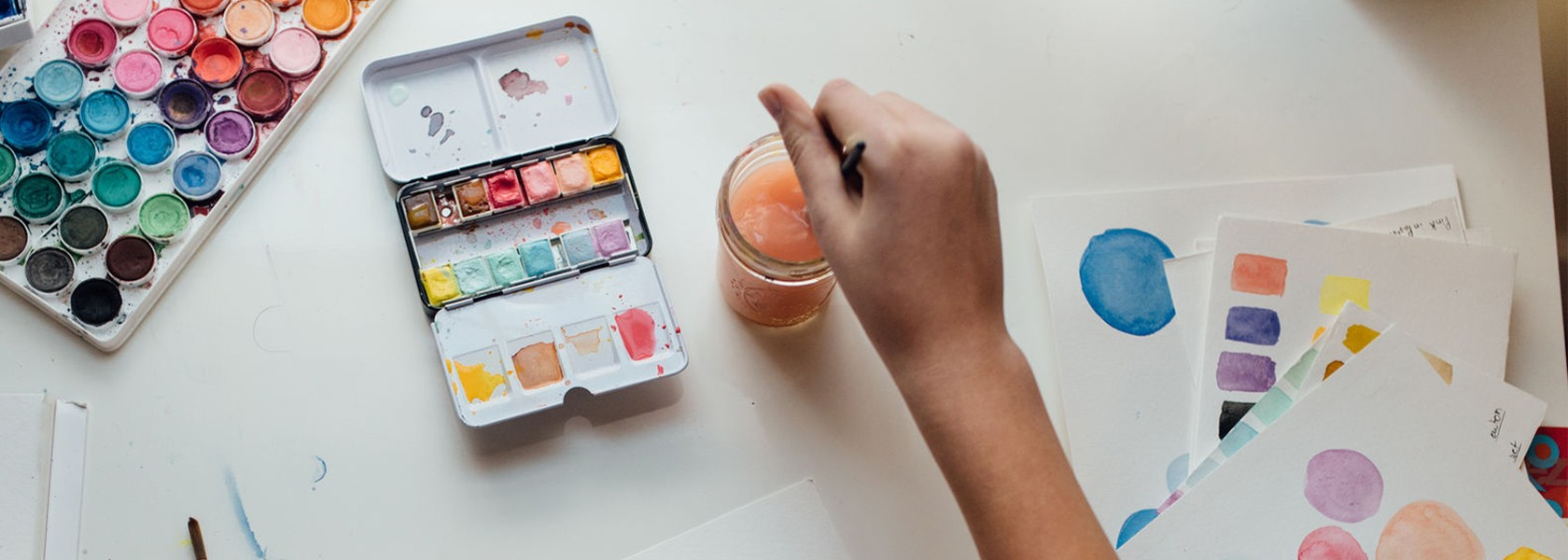 Frauenhände malen mit Wasserfarben