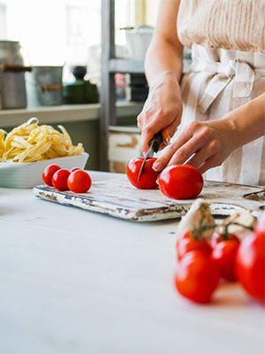Frau mit beige gestreifter Schürze schneidet Tomaten in der Küche, daneben steht eine weiße Schalte mit Pasta