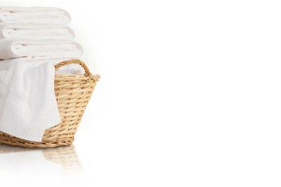 Ein geflochtener Korb voll mit weißer Wäsche.