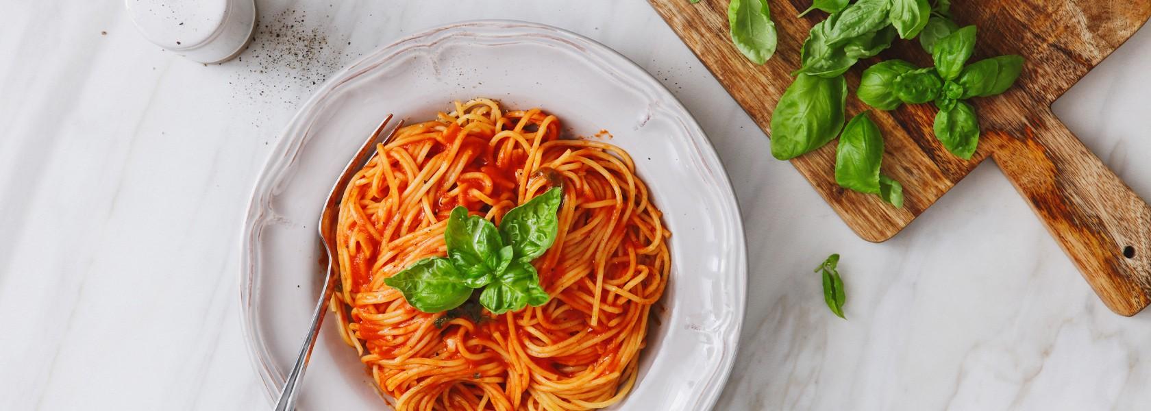 Ein Teller Spaghetti, verfeinert mit frischem Basilikum.