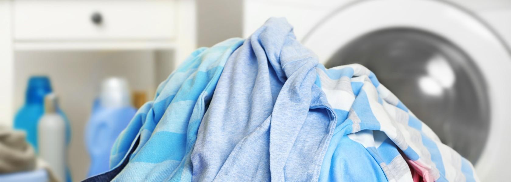 Ein Berg bunter Wäsche, im Hindergrund verschwommen eine Waschmaschine.