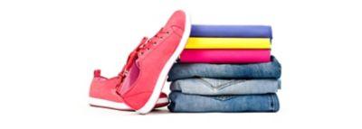 Tvarkingai sulankstytų drabužių krūva, jai iš kairės - medžiaginiai sportiniai bateliai.