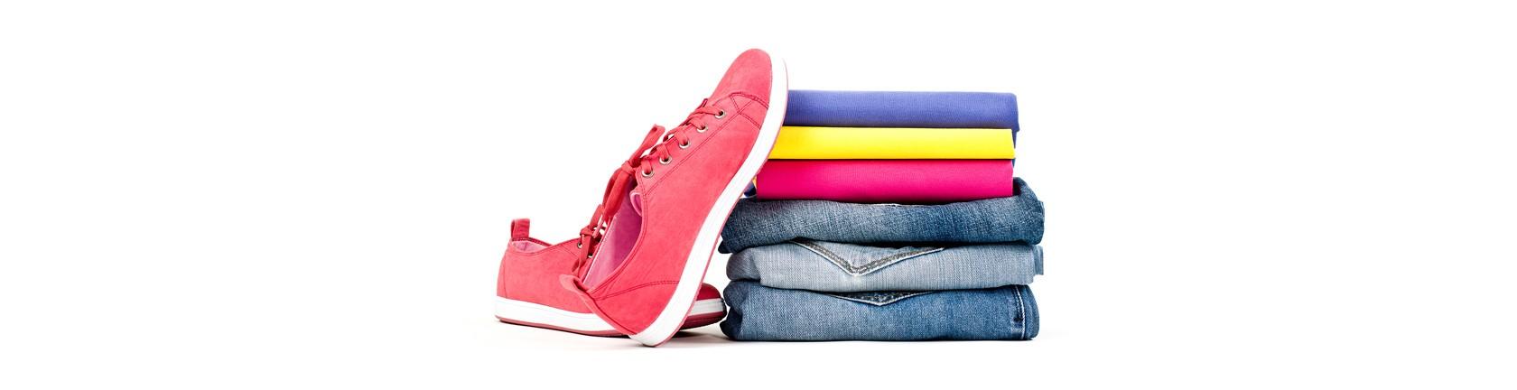 Ordentlich gefalteter Kleidungsstapel, links davon Sneaker aus Stoff.