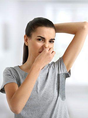 Frau in grauem T Shirt mit Schweißfleck unter dem erhobenen Arm hält sich angeekelt die Nase zu