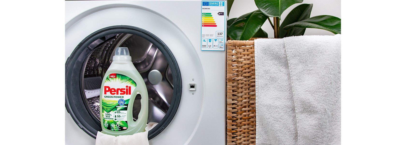 Persil Power Gel am Rand der Wäschetrommel auf einem Handtuch platziert.