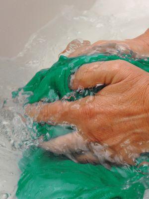 Hände waschen ein grünes Kleidungsstück in klarem Wasser
