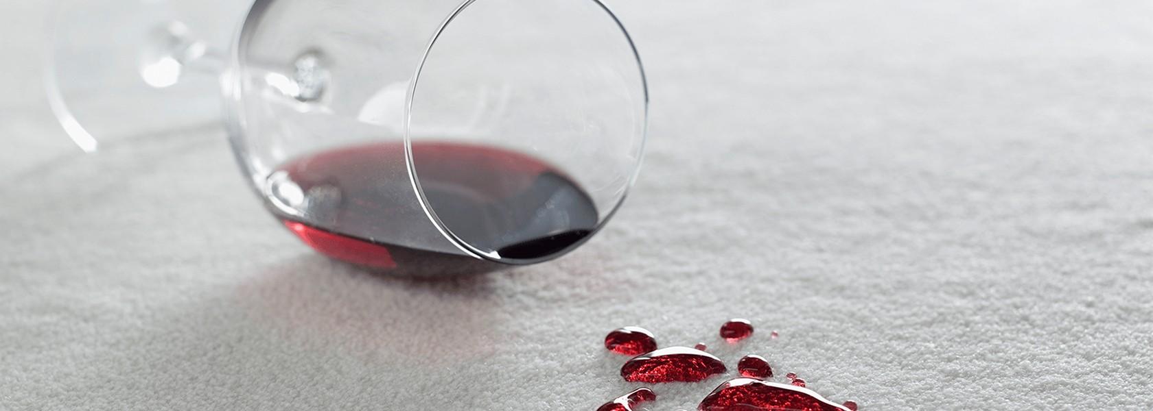 Ein umgekipptes Glas mit Rotwein, auf dem weißen Teppich einige Weintropfen.