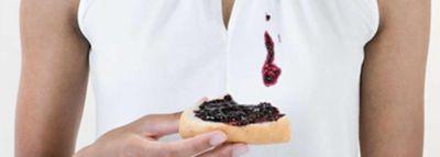 Kobieta w białej bluzce zaplamionej dżemem trzymająca kanapkę