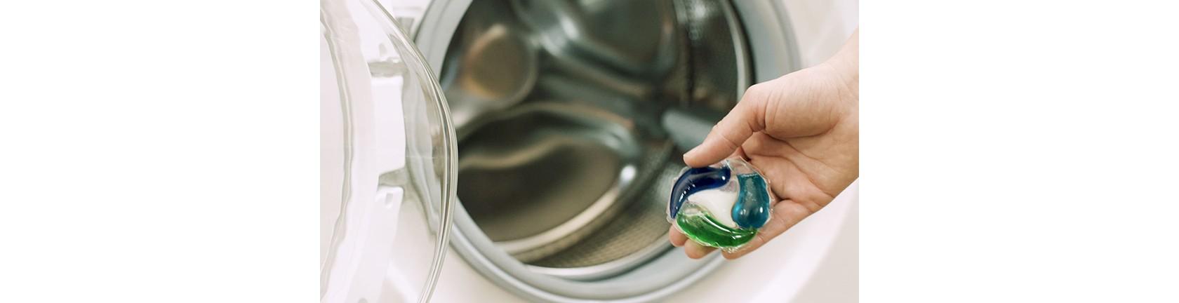 Ansicht einer Hand, die einen Persil 4in1 Disc hält, im Hintergrund eine Waschtrommel.