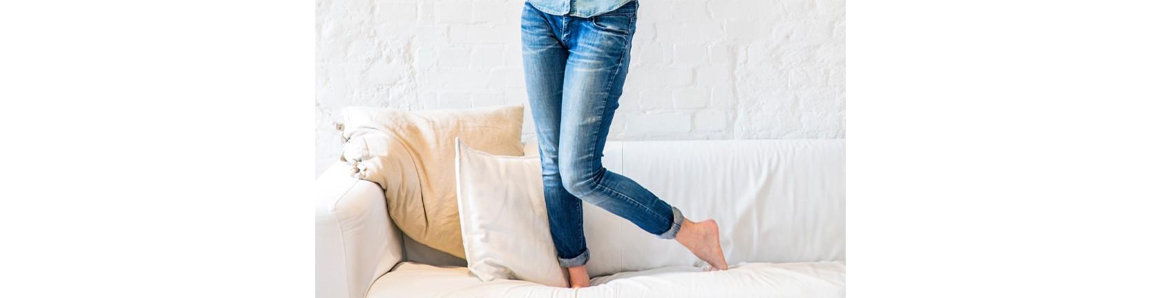 Eine Frau in Jeans steht auf einer hellen Couch, zu sehen sind nur ihre Beine.