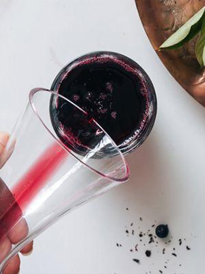 Heidelbeersaft wird aus einer Glaskaraffe in einen anderen Glasbehälter geschüttelt, daneben auf dem Tisch eine Schale voll mit Heidelbeeren.