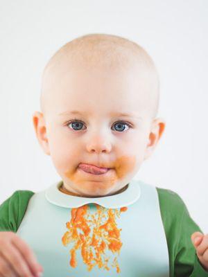 Kleinkind im orangefarbenen Langarmshirt und weißem Lätzchen vor weißem Hintergrund und verschmierter Mundpartie