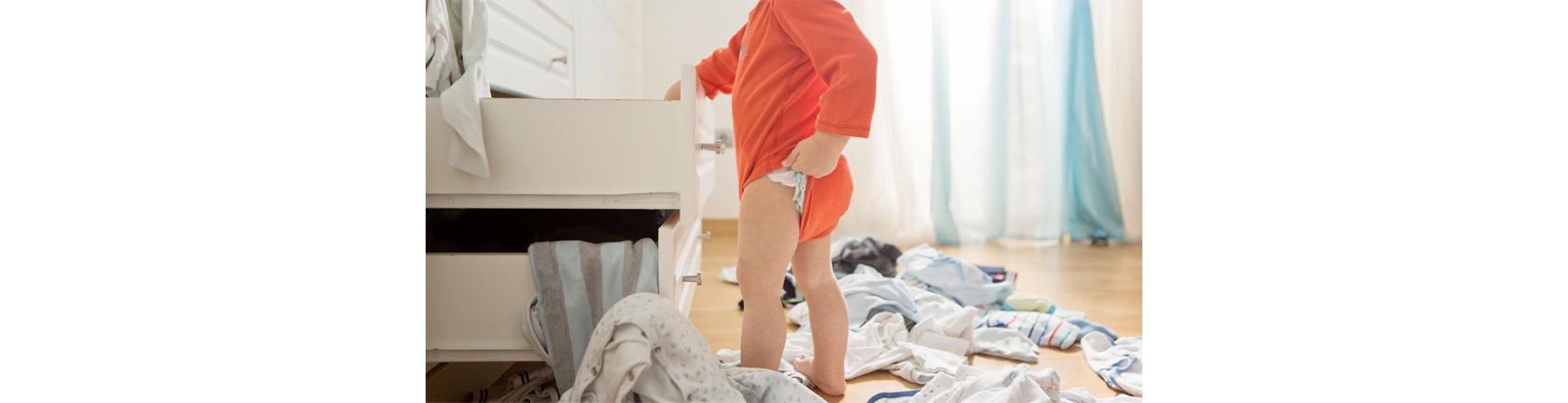 Ein Baby steht vor einer geöffneten Kommode und zieht sich  sein Body zurecht, im Hintergrund liegt Kleidung auf dem Boden.