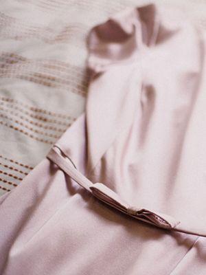 Ein pastellfarbenes Kleid aus empfindlichen Stoff liegt auf einer Bettdecke.