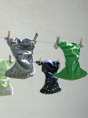 Farbige Stoffwindeln hängen an Wäscheleine mit Holzwäscheklammern befestigt