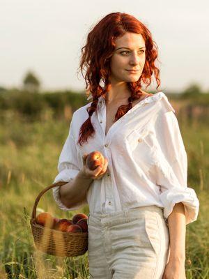 Junge rothaarige Frau mit weißem Leinenhemd und beigefarbener Hose steht in hohem Gras mit einem Korb voller Pfirsiche und einem Pfirsich in der Hand