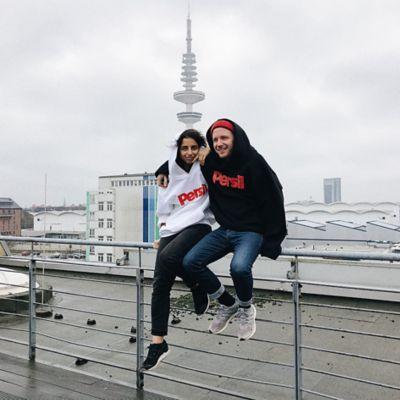 """Zwei Jugendliche in Kapuzenpullovern mit der Aufschrift """"Persil""""  sitzen Arm in Arm auf einer Brüstung."""
