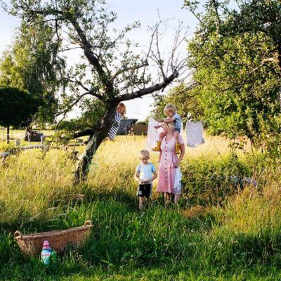Eine Mutter hängt mit ihren drei Kindern Wäsche im Garten auf.