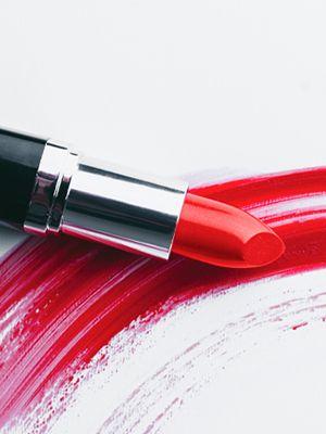Roter Lippenstift ohne Kappe liegt auf einem dicken, zum Halbkreis gebogenem, roten Streifen, der mit einem Lippenstift gemalt wurde.