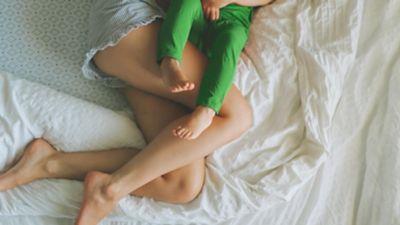 mutter und kleinkind auf bett mit matratzenbezug und weißer bettwäsche