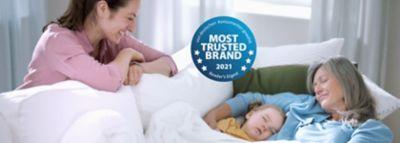 Eine frau schaut auf ein Baby und eine ältere Frau, die schlafend auf einer Couch liegen.