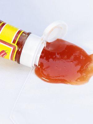 Eine umgekippte Ketchupflasche, aus der Ketchup ausläuft.
