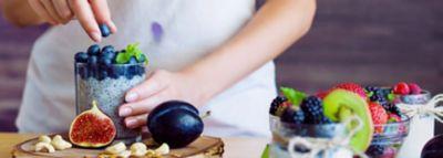Frau in weißem Shirt mit Blaubeerfleck legt Baubeeren auf Chiapudding im Glas