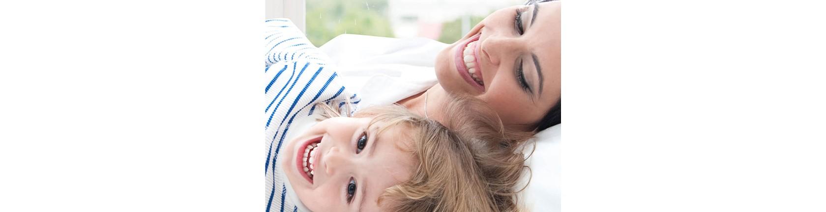 Eine Mutter mit ihrem kleinen Sohn, beide liegen auf dem Rücken und lachen herzlich.
