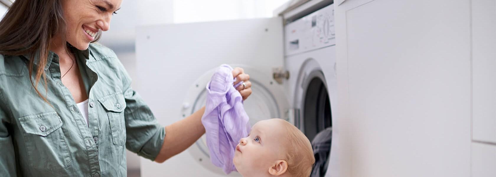 Eine Mutter schaut lachend und liebevoll ihr Baby an, während sie Wäsche aus der Waschmaschine rausholt.