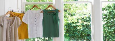 Bunte kleidungsstücke hängen auf kleiderbügeln vor einem fenster mit blick ins grüne