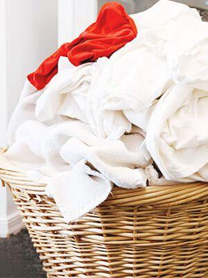 Beyaz çamaşır ve kırmızı bir giysi ile dolu hasır sepet.