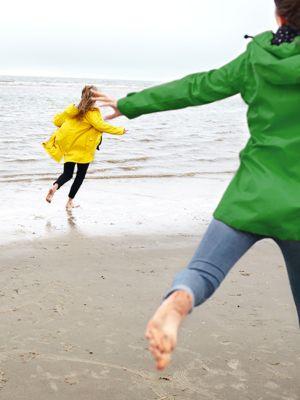 Frau mit gelber regenjacke und frau mit grüner regenjacke rennen am sandstrand