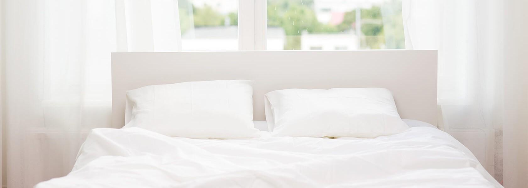 Ein Bett mit strahlend weißer Bettwäsche, das vor einem Fenster steht.
