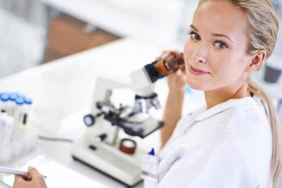 Μια γυναίκα με λευκή ποδιά εργαστηρίου στέκεται δίπλα από το μικροσκόπιο και κοιτάζει πάνω από τον αριστερό της ώμο στην κάμερα.