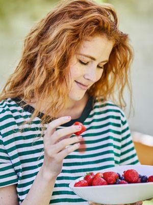 Junge Frau mit grün-weiß gestreifte T-Shirt hält eine weiße Schale mit Beeren in der einen und eine Erdbeere in der anderen Hand