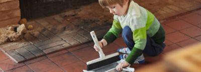 junge in gestreiftem pullover reinigt fliesenboden mit rußflecken
