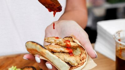 Eine Frau hält eine Art Taco mit Fleisch und tröpfelt Salsa-Sauce drauf, der Fokus liegt auf den Händen.