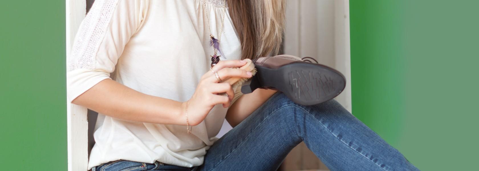 Frau in weißem Shirt pflegt ihre Stiefeletten mit Schuhcreme.