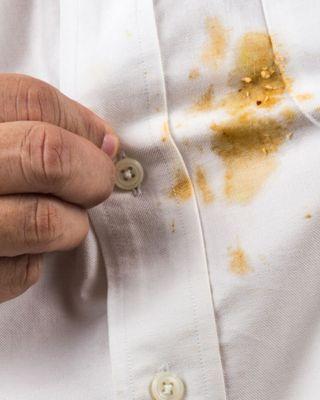 Mann in weißem Hemd mit orangefarbenen Essensflecken